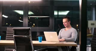 Two people working in a modern office at night