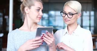 Two women talking in a modern office