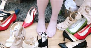 Woman Chooses  Shoes At Fashionable Shop