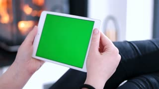 Woman using green screen tablet computer at modern villa