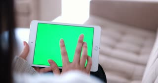 Woman using tablet computer with green screen. Close up shot of woman's hands with pad