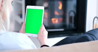 Woman using vertical tablet computer with green screen. Close up shot of woman's hands with pad