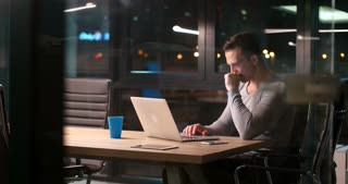 Young Businessman Working On Laptop Sitting In Office late at Night