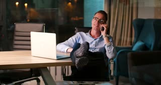 Young Businessman Working With Smartphone And Laptop In Office At Night