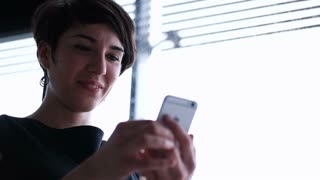 Young businesswoman with smartphone in the office