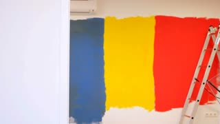 Young Couple Decorate Their New Apartment and painting wall
