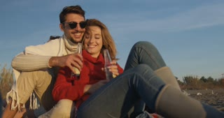Young Couple Relaxing By The Fire, Drinking A Beer at beach