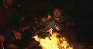 Young Couple Sitting Around Campfire At The Beach At Night drinking beer