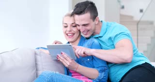 Young Couple Using Electronic Tablet At Home on sofa