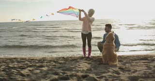 Young Couple with dog Flying A Kite On A Beach during autumn