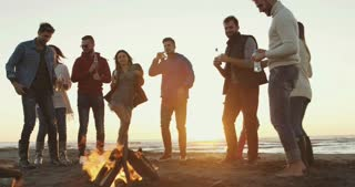 Young Friends Making A Toast With Beer and having fun Around Campfire at beach party