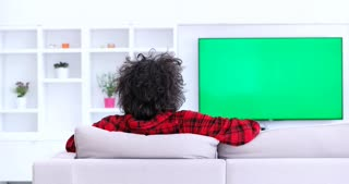Young Man Watching Television Green Screen In Living Room. Green screen devices