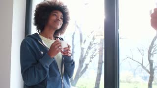 Young Mixed Race Couple relaxing with coffee in Apartment Big Window Morning Sunlight