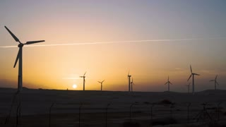 4K Beautiful windmill turbines harnessing clean, green, wind energy silhouetted in the sunset sky with sun rays. Green energy.