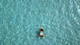 Aerial view. Beautiful young woman in white bikini floating on water surface in crystal clear turquoise color ocean