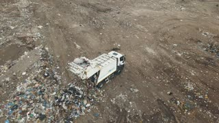Aerial view. City dump. The garbage truck in the dump. Aerial drone shot of the ecological damage. Flight over the urban refuse dump. Big piles of garbage trash.