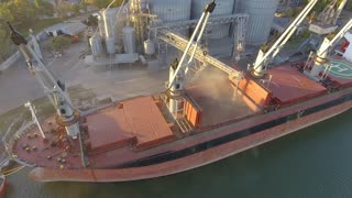 Aerial view of big grain elevators on the sea. Loading of grain on a ship. Port. Cargo ship