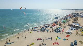 Aerial view of kitesurfing extreme sport with the wind freestyle. Beautiful top view of nice beach. Lots of kites