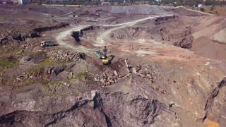 Aerial view of working excavator in the opencast mine. Camera flight over industrial landscape.