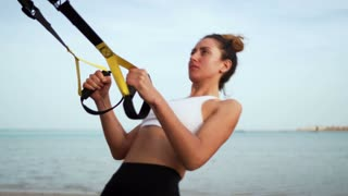 athletic, sexy young woman, doing exercises with fitness trx system, TRX suspension straps. On the beach, in summer, in sun rays.