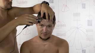 Barber cuts the hair of the client