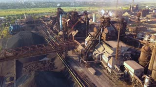 Blast furnace view from the air. Old factory. Aerial view over industrialized city with air atmosphere and river water pollution from metallurgical plant near sea.