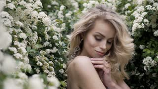 Blonde bride in fashion white wedding dress with makeup. Wedding day of bride in bridal gown. Beauty woman and flowers. Fashion blonde model indoors. Beauty portrait of model in white bridal dress