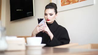 Close-up of young professional businesswoman using smartphone and drinking coffee