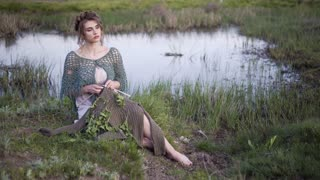 Fairy tale. The charming girl sitting in the fairy lakeshore. Knitting