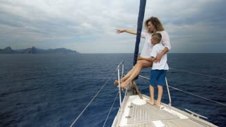Freedom of the ocean for healthy family on outdoor Summer vacation sailing on luxury yacht. Mother and son