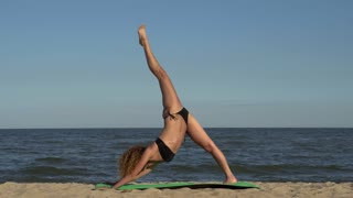 Girl doing yoga on the beach. Yoga on the beach