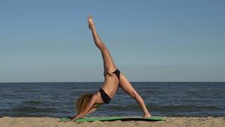 Girl doing yoga on the beach. Yoga on the beach