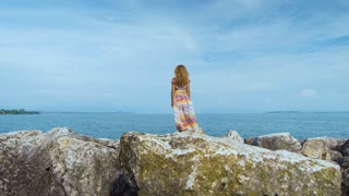 girl in a beautiful dress is standing on the coast
