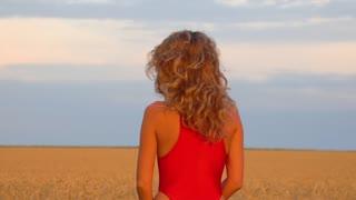 Girl in a field in a red swimsuit. Slowmo 120fps