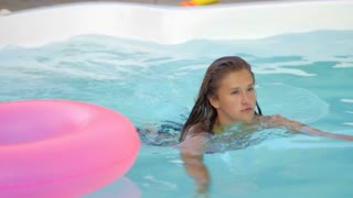 Happy girl relaxing on inflatable pink doughnut float. Young woman in bikini enjoying summer vacation drinking cocktails on pink floatie in pool