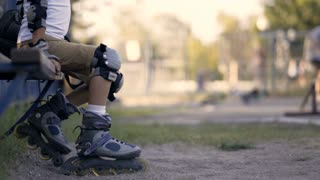 Legs of a child in roller skates. The child rolls on rollers.