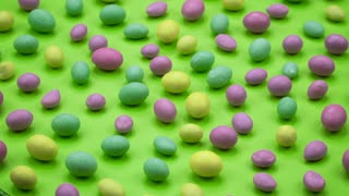 Macro video of tasty crispy round candies isolated on green background. Yellow, orange, green, pink and blue sweets rotating. Real time 4K