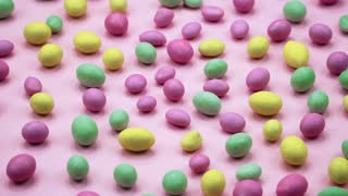 Macro video of tasty crispy round candies isolated on pink background. Yellow, orange, green, pink and blue sweets rotating. Real time 4K