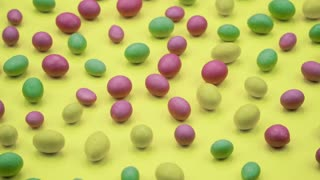 Macro video of tasty crispy round candies isolated on yellow background. Yellow, orange, green, pink and blue sweets rotating. Real time 4K