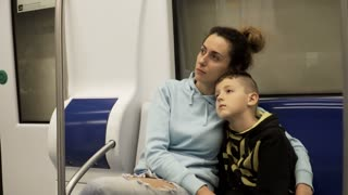 Mother and son traveling by subway train. Tired and sleepy boy lying on moms lap, woman stroking his head