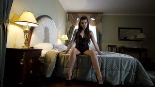 Passionate beautiful model lying on the bed in the hotel and posing for photos