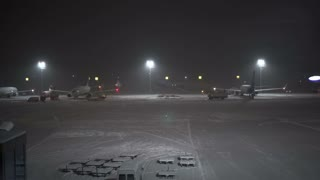 Snowstorm at the airport. Workers and service cars work near aircraft