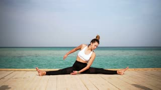 The girl is making yoga pose on beach of the island. Static. Sea or ocean happy woman relaxation. Water and clouds. Hands and blue sky.