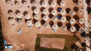 Umbrellas, deck chairs and tourists relaxing on the beach. Aerial top view.