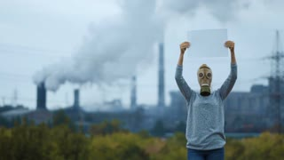 Woman in a gas mask on a background of smoky pipes of a factory