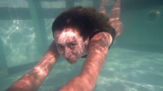 Woman in blue bathing suit swimming underwater in slow motion