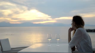 Woman sipping white wine and enjoying the view of a beautiful golden summertime sunset.