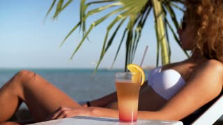 Young girl in bikini on beach with party cocktail