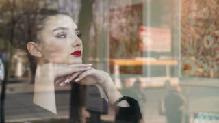 Young woman looking outside through the window in a coffee shop. She looks happy. We see traffic and people in the reflection of the window.