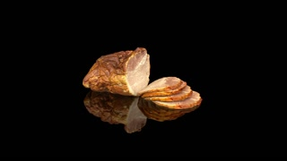 Sliced cold baked pork isolated on black in slow motion.